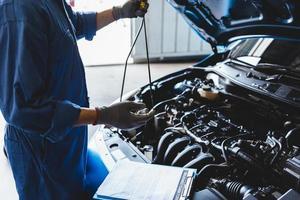meccanico di auto che tiene il controllo dell'olio del cambio per la richiesta di manutenzione del cliente foto