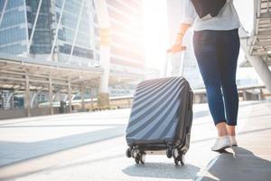 Turista viaggiatrice che cammina con i bagagli alla stazione terminale foto
