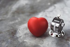 cuore e contatore alla rovescia sulla superficie del tavolo in marmo foto