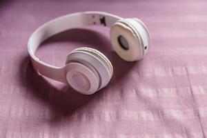 cuffie bianche su sfondo viola. concetto di musica. foto