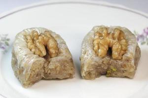 delizioso baklava di noci su un piatto bianco foto