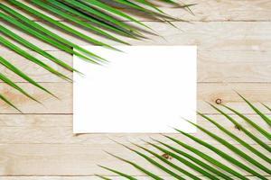 vista dall'alto carta bianca vuota con foglia di palma su tavola di legno foto