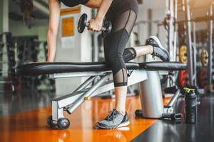 Giovane donna panca con manubri in palestra fitness foto