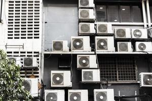un sacco di vecchi condizionatori d'aria sporchi su un muro sporco. foto