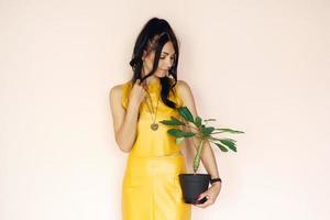 la bella donna tiene il fiore in vaso su un fondo rosa foto