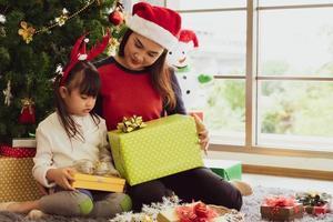 la madre asiatica dà il regalo di Natale alla figlia foto