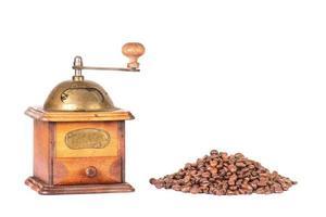 macinacaffè con montagna di chicchi di caffè foto