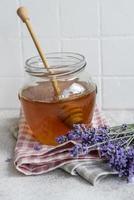 vasetto con miele e fiori di lavanda fresca foto