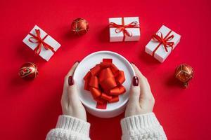 le mani tengono una bella confezione regalo con fiocco su sfondo rosso. foto