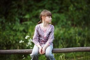 bambina seduta su una staccionata di legno foto