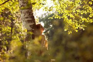 giovane donna felice in piedi vicino a betulla? foto