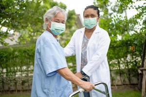 il dottore aiuta il paziente asiatico della donna anziana al parco? foto