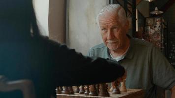 ragazza e uomo che giocano a scacchi al tavolo foto