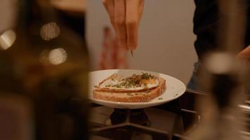 mani della donna che organizza uovo fritto ed erba cipollina sul panino foto