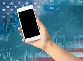 tenendo in mano il telefono cellulare per finanziare il commercio online con la bandiera americana foto