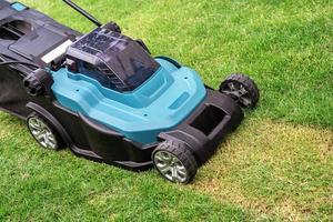 la macchina per il movimento del prato taglia l'erba verde, piantagione di hobby nel giardino di casa foto