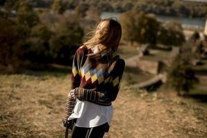 giovane donna in piedi fuori alla soleggiata giornata autunnale foto