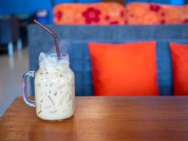 tè al latte fresco in un bicchiere posto su un pavimento di legno. con spazio libero foto