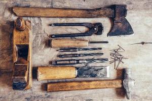 vecchi strumenti di costruzione su un banco di lavoro in legno piatto sfondo laici foto