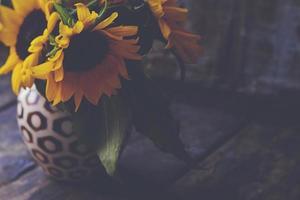 primo piano di fiori gialli su un vecchio tavolo di legno vintage foto