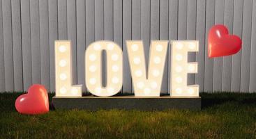 cartello d'amore con lampadine su un giardino foto