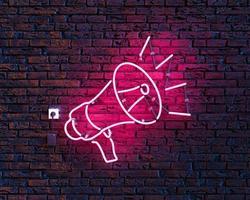 megafono al neon sul muro di mattoni foto