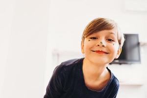 ragazzo carino con la faccia dipinta da clown, sorridente foto