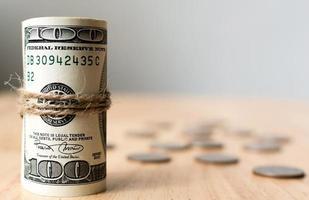 Rotoli la banconota del dollaro dei soldi con le monete sul tavolo foto