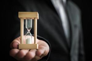 mano dell'uomo d'affari che tiene la clessidra, concetto di gestione del tempo foto