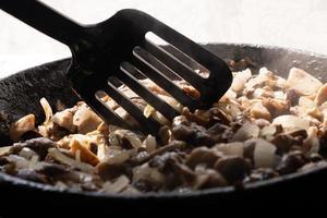 cucinare funghi fritti con cipolle, mescolare i funghi foto