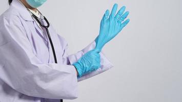 indossare i guanti. il medico asiatico indossa un guanto per le mani in nitrile di gomma blu. foto