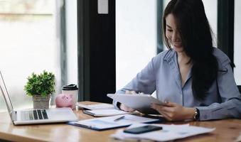 donna asiatica d'affari che utilizza laptop per fare finanza matematica su legno foto