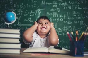 ragazzo preoccupato in classe con le mani sulla testa foto