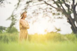 giovane donna in piedi tempo felice nel campo in erba. foto
