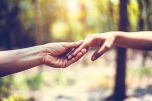 primo piano della mano amica dell'essere umano durante il viaggio nella foresta foto