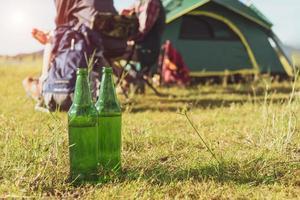 primo piano di una bottiglia di birra in un prato durante il campeggio all'aperto foto