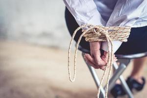 primo piano della mano della donna con la corda del legame. concetto di ostaggio e riscatto foto