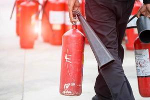 la parte inferiore del corpo del vigile del fuoco prepara l'esercitazione antincendio tenendo l'estintore portatile foto