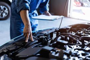 meccanico di auto che tiene appunti e controlla il veicolo di manutenzione foto