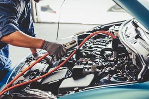 meccanico di auto che tiene la batteria di elettricità attraverso i cavi jumper foto
