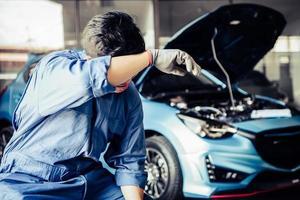 meccanico di auto che riposa dalla stanchezza e si asciuga il sudore dalla stanchezza foto