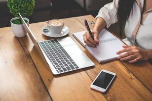 primo piano di una donna d'affari che lavora con documenti e laptop foto