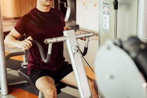 vista frontale dell'uomo sportivo che utilizza la macchina per allungare i muscoli della schiena foto