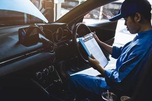 meccanico che tiene appunti controllando all'interno dell'auto al veicolo di manutenzione foto