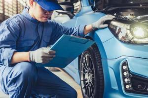 tecnico meccanico di auto asiatico che tiene appunti per controllare la manutenzione foto