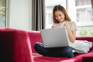 giovane donna che naviga in internet con il computer portatile sul divano rosso foto