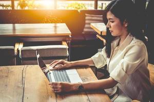 donna asiatica che lavora con il computer portatile nella caffetteria? foto