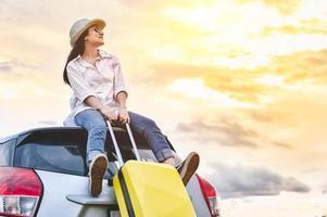 donna asiatica felice sopra l'auto con la borsa dei bagagli? foto