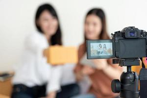primo piano della videocamera digitale che registra due ragazze che presentano foto
