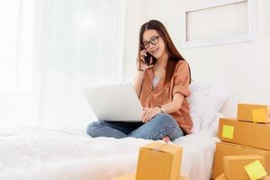donna asiatica di bellezza che usa il computer portatile e chiama il telefono sul letto? foto